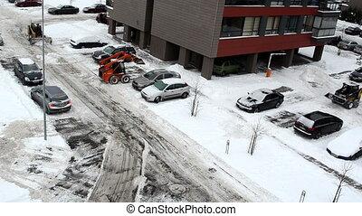 tractors excavators clean snow between flat block houses cars on street parking lot lantern circa December 2012 in Vilnius.