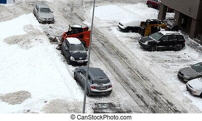 two tractor excavator work clean snow between flat block houses on street parking lot lantern circa December