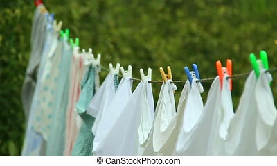 Clean Washed Clothes hanged on wire with clothes peg and Spring Nature background