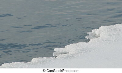 Clean water flows slowly in deep pond with thaw in early...