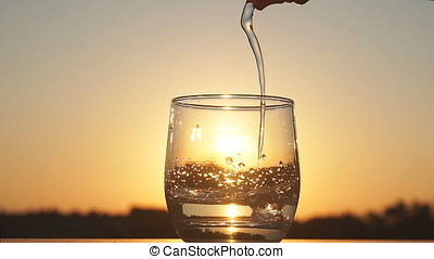 Clean water is poured into a glass at sunset. Slow motion