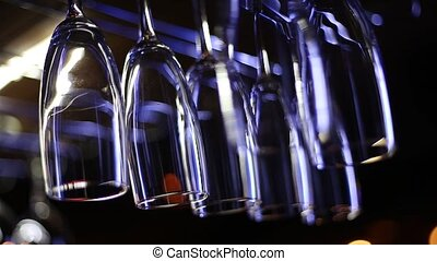 clean wine glasses - Clean wine glasses hang over the bar in...