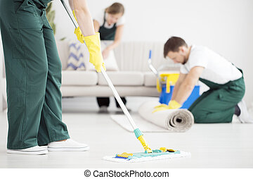 Cleaner cleaning floor using mop
