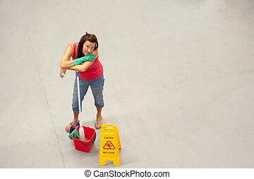 Cleaner mopping office warehouse floor - Overhead portrait...