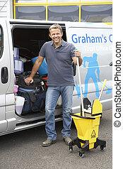 Cleaner standing next to van
