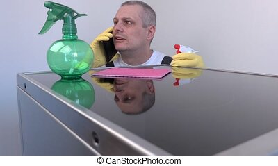 Cleaner talking on smart phone near surface of electric...