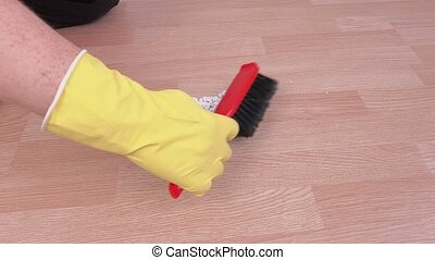 Cleaner with brush and scoop collect rubbish on the floor