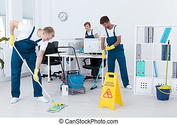 Cleaners cleaning an office - Young contract cleaners...