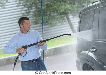 cleaning a car with high pressure cleaning in car wash