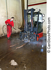 Cleaning a forklift - Man cleaning a forklift using a high...