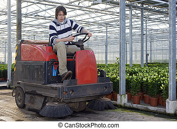 Cleaning a glasshouse - A man on an industrial cleaning...