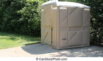 Cleaning a portable bathroom - A maintenance worker with a...