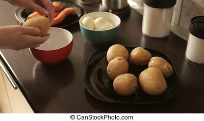 Cleaning boiled potatoes for dinner preparation. Healthy...