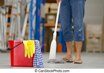 Business cleaning of industrial warehouse with isolated red bucket, yellow glove and legs of female cleaner in blurred background and copy space.