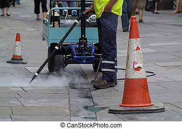 Steam cleaning pavement sidewalk of gum spewed out by yobs