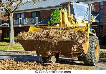 Cleaning city during autumn time fallen autumn leaves from the road sidewalk with a tractor