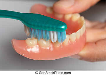 Cleaning denture or dental prothesis with toothbrush -...
