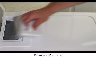 Cleaning Dryer Lint Trap - Male caucasian hand pulls out and...