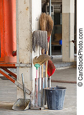 Old and dirty cleaning equipments in car garage, bucket, scoop, broom and mob