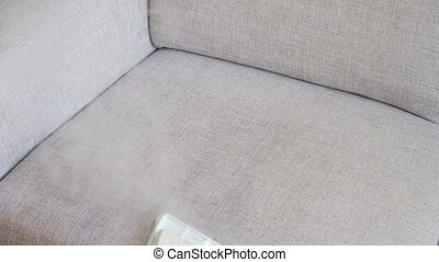 Cleaning fabric of the sofa with a steam cleaner.