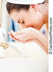Cleaning face in the bathroom with water