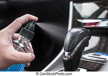 Cleaning gear lever with alcohol sanitizing spray in a car for protection disease and antibacterial , Coronavirus (COVID-19) prevention concept