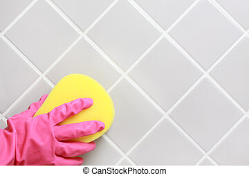 Cleaning. - Hand and glove cleaning the bathroom tiles.