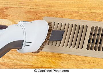 Cleaning heater vent withVacuum - Horizontal photo of vacuum...