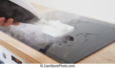 Cleaning kitchen hob with a steam cleaner.