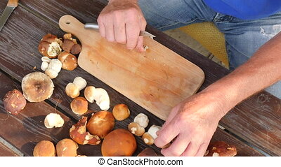 Cleaning of wild mushroom with kitchen knife in old hands. Man hands take carefully mushroom and remove clay or roots from stem