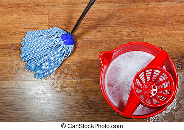 cleaning of wooden floors and red bucket with washing water