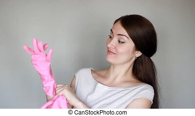Cleaning. Portrait of a young woman in overalls close-up. The girl smiles, shows how she puts rubber gloves on her hands and looks into the camera and is about to clean