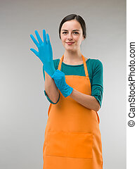 cleaning preparation - young happy cleaning woman putting on...