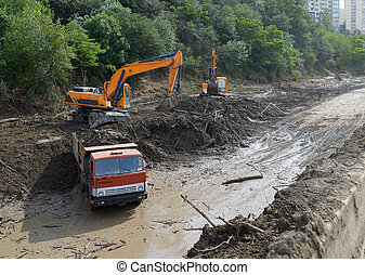 cleaning road by landslide excavator and trucks