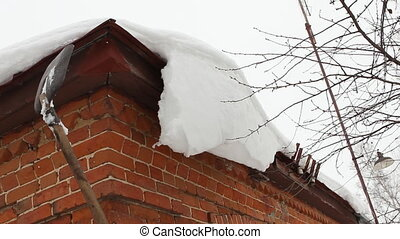 Cleaning snow from roof eaves cornice - countryside house