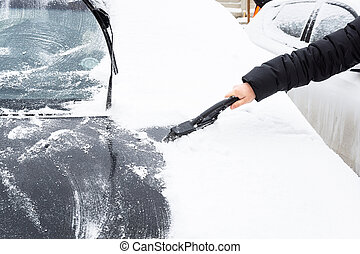 Removal snow from car body with brush, man cleans the car from snow after snowfall