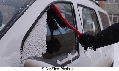 Cleaning the car windows off the snow - Man is cleaning the...