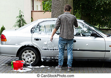 Cleaning the car - Young man cleaning his car on the...