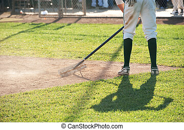 cleaning the pitcher\'s area after a game
