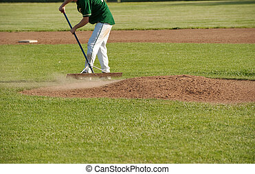 cleaning the pitcher\'s mound after a game - a baseball...