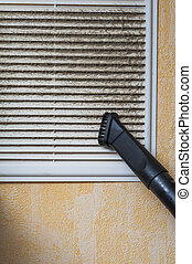 Cleaning ventilation grill with vacuum cleaner