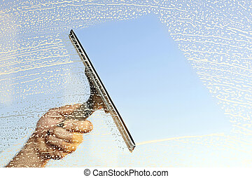 Cleaning windows - A hand and a squeegee cleaning windows