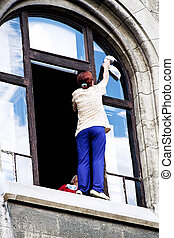 Cleaning windows. Hazardous household work - A woman washing...