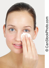 Cleansing Routine - Young woman cleancing her face and...