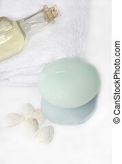 cleansing spa treatment with massage oil bottle corked, white bath towel and pebble shaped candles