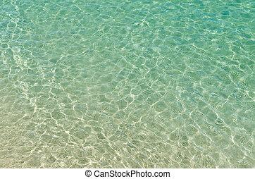 clear beach ripple water reflecting in the sun