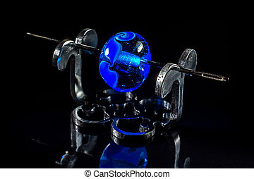Clear blue glass bead on stand