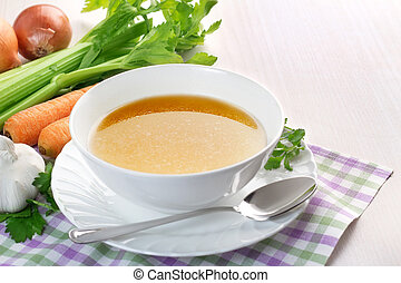 clear broth - bowl of broth and fresh vegetables on wooden...