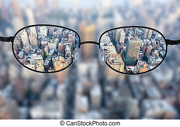 Clear cityscape focused in glasses lenses with blurred ...