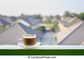 Clear coffee cup on balcony and blurred view of building